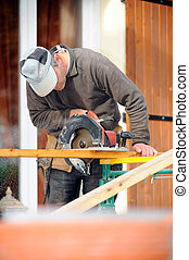 Man using circular saw on construction site