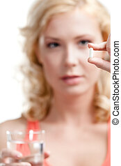 Girl takes painkillers - Blond woman with glass of water...