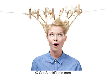 Woman with creative hairdo of clothes pegs