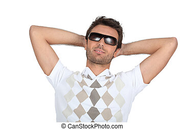 Man wearing sunglasses with his hands behind his neck
