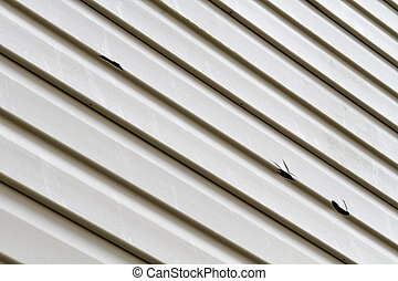 Vinyl Siding Panel Damaged By Hail Storm - Angled shot of a...