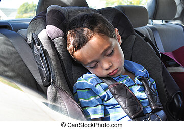 young boy sleeping in carseat in car