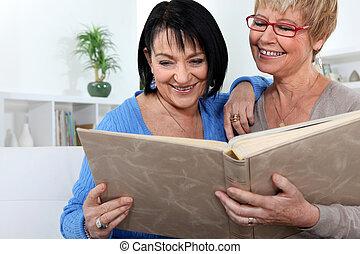 Two women looking through family photo album