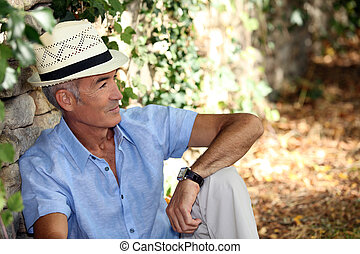 Elderly man sitting against the stone wall