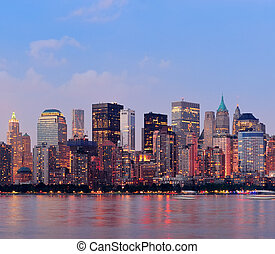 New York City Manhattan downtown skyline at sunset over...