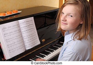 Piano player - Young blond girl plays piano