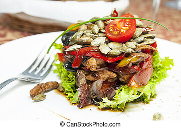 warm salad of vegetables and meat on a plate in a restaurant