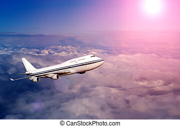 passenger airplane in the clouds at sunset or dawn. travel...