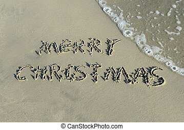 Merry Christmas handwritten in sand on a beautiful beach