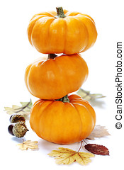 pumpkins - Three stacked mini pumpkins with fall leaves over...