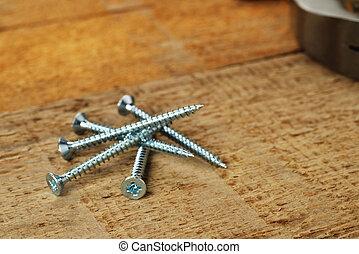 steel screws on  wooden background.