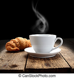 hot coffee and croissant on rustic table and black...