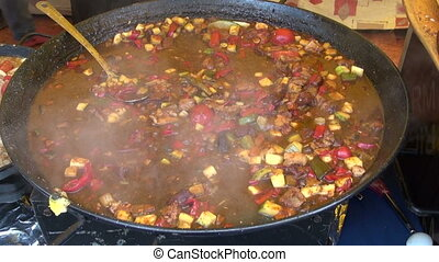 Meat and vegetable stew cooking in a big cast iron pot