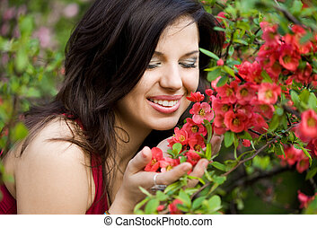 woman in garden with red flowers