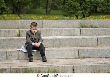Serious - Boy with serious expression sitting on step