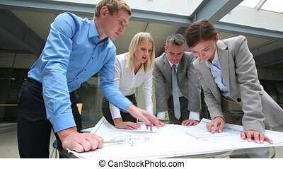 Close look at blueprint - Team of architects taking a close...