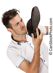 Man holding one of his shoes close to his nose - Young man...