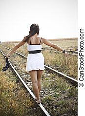 Picture of young woman with sandal in hand on the railway