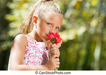 Blue eyed girl smelling flower outdoors.