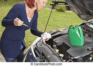 Checking oil level in the vehicle - Cute woman driver...