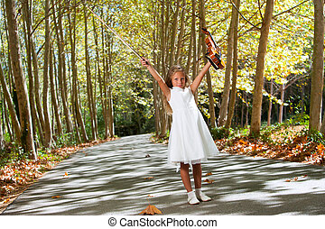 Full length portrait of young violinist in woods.