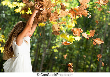 Girl playing with autumn leaves outdoors.