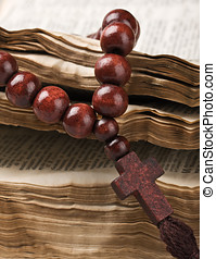 wooden rosary are on an old bible