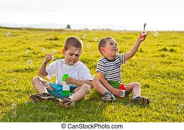 Boys blowing soap bubbles