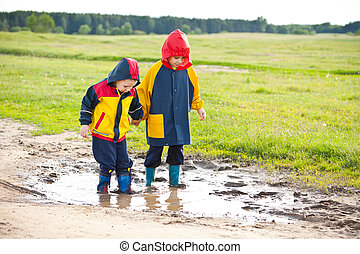 Little boys walking in a mud puddle