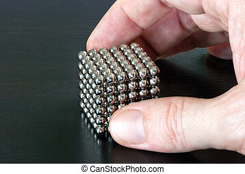 Hand Picking Up Cube of Magnetic Balls - Close-up of a hand...