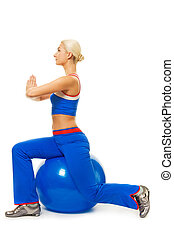 Beautiful woman doing yoga exercise on the ball