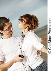 Happy young couple listening to music together