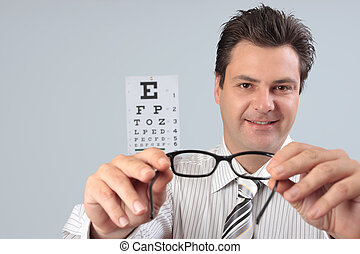 Eye doctor holds glasses - An optometrist trying eyeglasses...