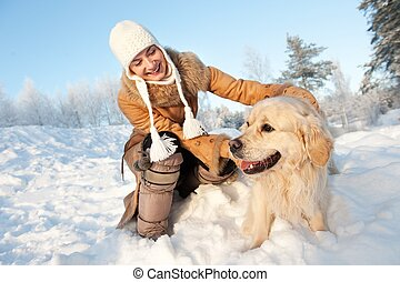 Happy woman playing with golden retriever outdoors