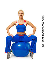 Young happy woman doing exercise on a fitness ball