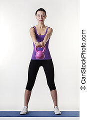 work out - young woman working out with a bell weight to...