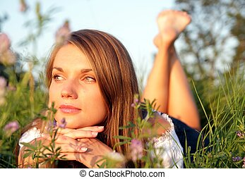 Attractive young woman lying in a flower meadow