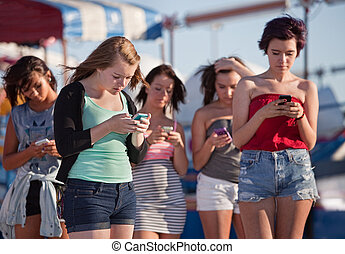 Young Ladies Using Their Phones - Young woman at amusement...