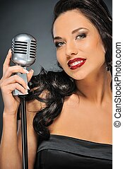 Beautiful brunette woman with a retro microphone