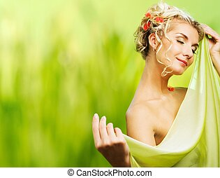 Beautiful young woman with fresh flowers in her hair. Spring...