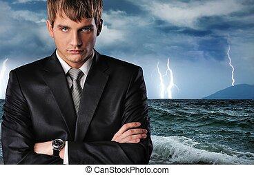 Ocean storm - Seriour businessman over dark stormy sky