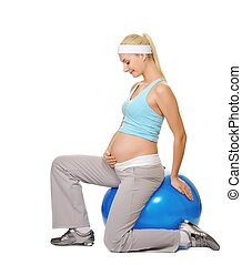 Young pregnant woman making exercise on a fitness ball