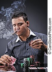Portrait of a young gangster smoking and playing poker