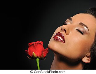 Portrait of a beautiful woman with a red rose