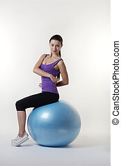 the gym ball - fit looking young woman doing stretching...