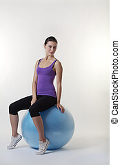 the gym ball - woman sitting on a gym ball about to do a...