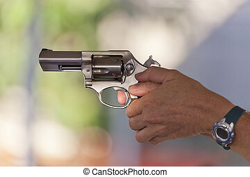 Firing a Stainless Steel Revolver - Woman holding a...