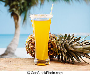 pineapple juice and pineapple on the beach