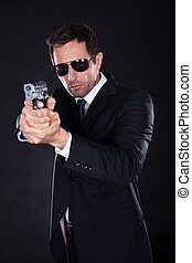 Portrait Of Young Man With Gun On Black Background