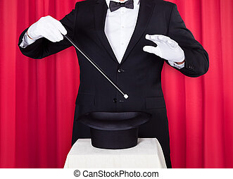 A Magician In A Black Suit Holding An Empty Top Hat And...